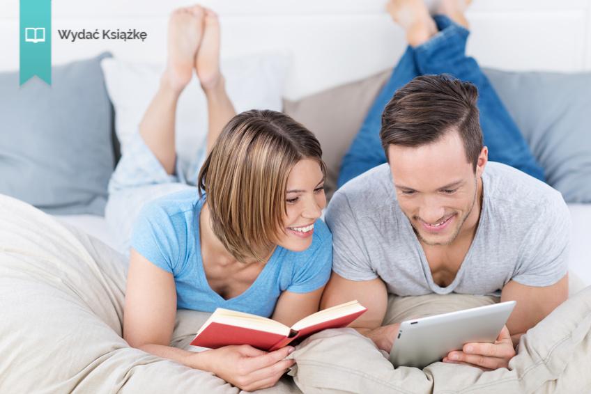 lachendes paar mit tablet-pc und buch im bett